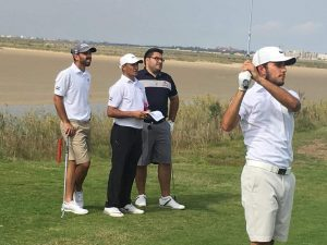 Saif Thabet, National Team Coach Samir Wallain, and Khalid Yousuf look on as Ahmed Skaik hits an iron shot at The Residence Tunis Golf Course during the first practice round.